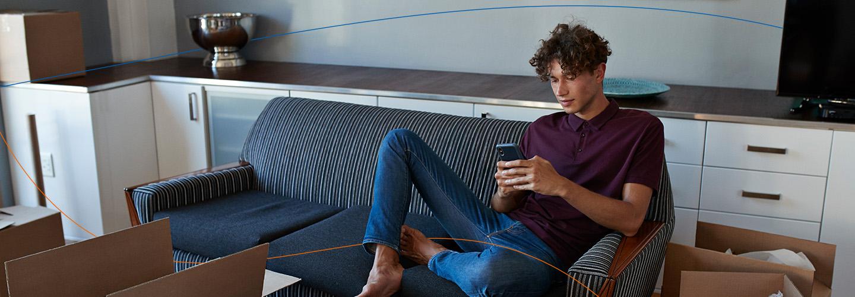 Gruppe junger Menschen sitzt in einer Wohnung auf dem Boden. Ein Mann schaut auf sein Mobiltelefon.